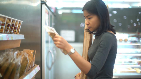Young Thai woman is buying bread in bakery shop Live Action