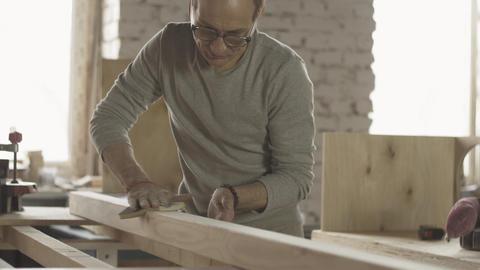 Adult woodworker polish wooden board surface by special sponge. Manufacturer Live Action