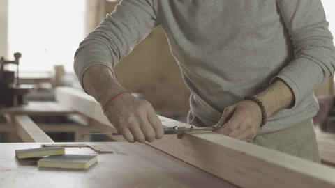 Adult locksmith measures wooden board by special ruler. Furniture. Woodworker Live Action