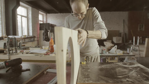 Professional woodworker connects two wooden polished boards. Furniture. Assembly Live Action