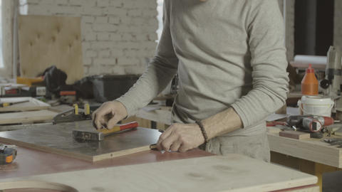 Professional woodworker drive in dowel into wooden board. Furniture. Assembly Live Action