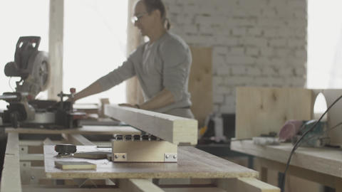 Woodworker put edge of long wooden board under circular saw. Furniture Live Action
