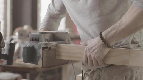 Woodworker treats edge of wooden board by belt sander. Manufacturer Live Action