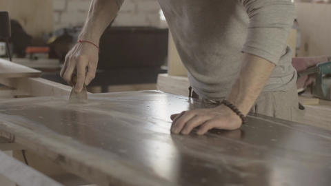 Woodworker scratch surface of wooden board by scraper handware. Manufacturer Live Action