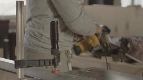 Professional woodworker hard fix metal balk on wooden board. Making furniture Live Action