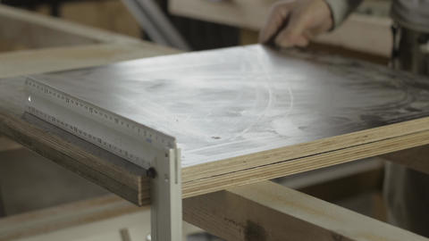 Woodworker put two equal wooden boards under metal straightedge. Furniture Footage