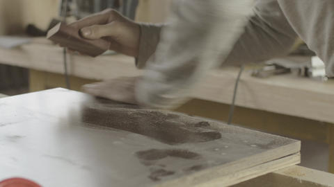 Professional woodworker polish edge of two wooden boards by special sponge Live Action