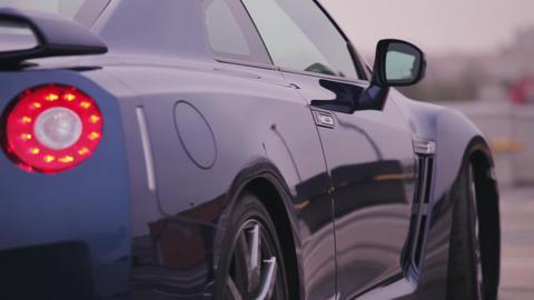 Back side of dark blue new car. Wheels. Presentation. Red lights. Bumper. Automo Footage