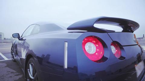Back side of new dark blue coupe car on street. Bumper. Presentation. Red lights Footage