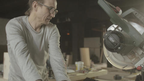Professional carpenter cut part of wooden board by circular saw. Woodworker Live Action