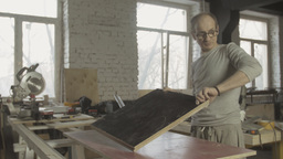 Professional adult carpenter connects two equal wooden boards on working table Footage
