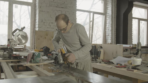Woodworker fixing circular saw on edge of wooden board on work table Live Action