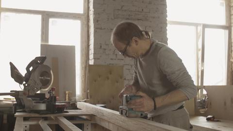 Woodworker in glasses treat wooden board by belt sander. Manufacturer Live Action