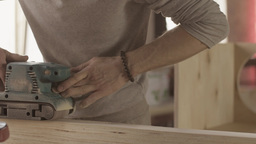 Aged woodworker careful process smooth of wooden board by belt sander Live Action