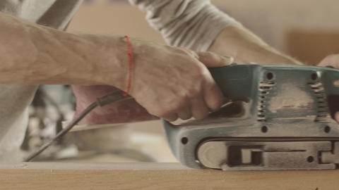 Adult woodworker process wooden board by belt sander. Smooth movements Live Action