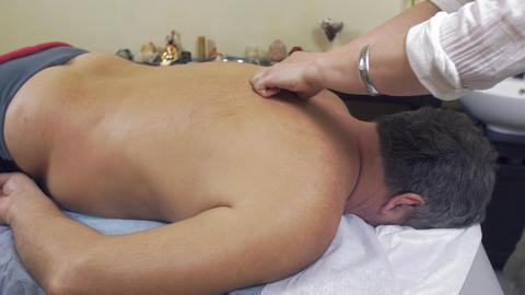 Masseuse make therapeutic massage of backbone to adult fat man. Medium shot Live Action