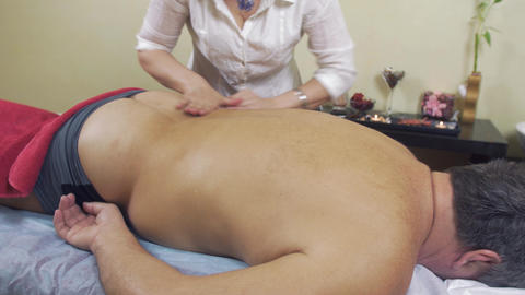 Masseuse make remedial massage of back to adult fat man. Medium shot Footage