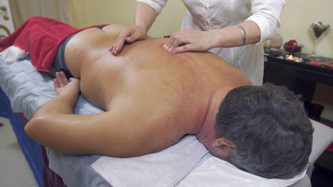 Masseuse press backbone of adult fat man. Therapeutic massage. Medium shot Live Action