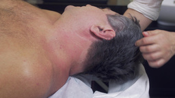 Close up of masseuse hands make therapeutic massage of head to adult fat man Footage