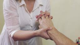Close up of masseuse hands make massage of hand wrist to adult man. Healing Footage