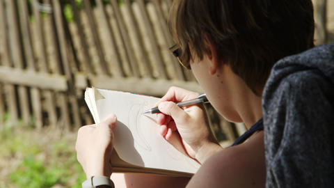 Girl artist in sunglasses draws sketches in notebook 影片素材