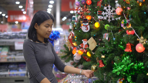 Woman is touching christmas tree decorations in supermarket Footage