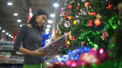 Young Thai Girl is choosing christmas decorations in supermarket Live Action