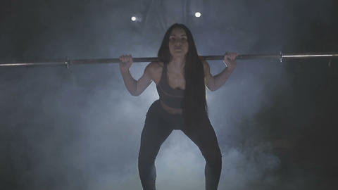 Full length image of a young woman testing her strength by holding a barbell Live Action