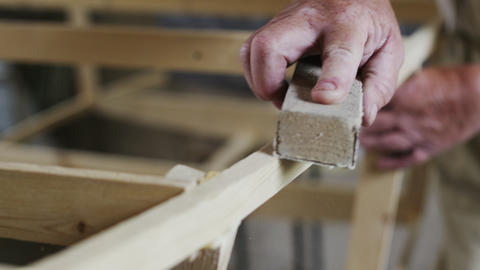 Elderly man carpenter builds a small boat with his hands out of wood in a small Footage