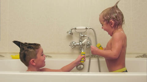 Two little boys having fun while taking bath in bathtub Footage