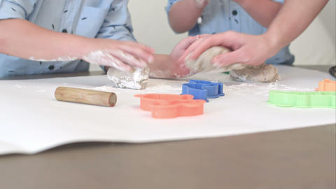 Two boys preparing dough for cookies together with their mum Footage