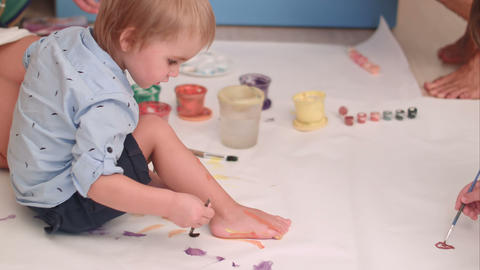 Cute little baby boy painting his feet on a large blank white paper Footage