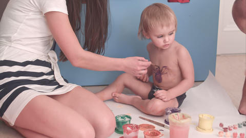 Mother painting a spider on her little boy Footage