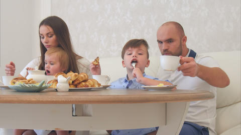 Happy young family enjoying tea with sweets at restaurant or cafe or home Footage