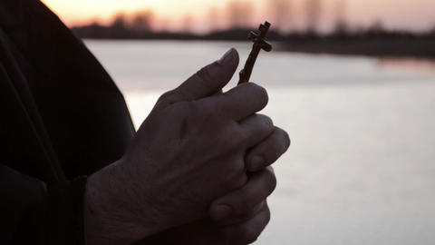 The hands of a monk holding a cross Live Action