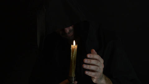 A bearded monk reads a prayer by candlelight, the flame of a candle sways 4 Live Action