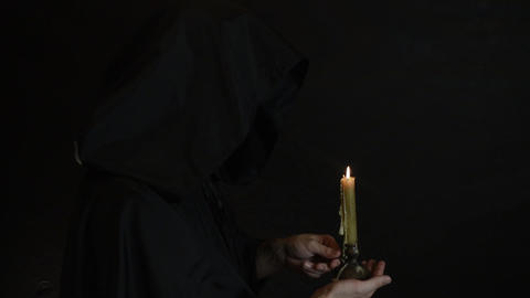 A bearded monk reads a prayer by candlelight, the flame of a candle sways 5 Live Action