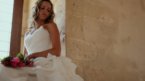A beautiful bride sits near a window in an old castle Footage