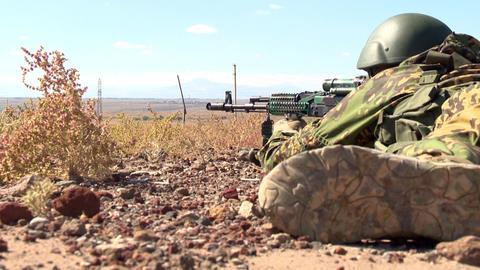 In the military helmet aiming a machine gun, lying on the sand in ambush Archivo