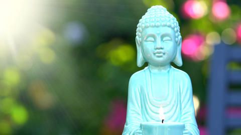 Aqua blue Buddha statue in colorful garden setting, with burning flame, static ビデオ
