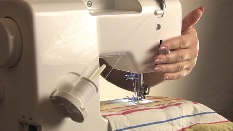 A seamstress prepares a sewing machine, sew the fabric Live Action