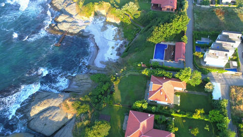 Aerial Flying Over Beautiful sea ,houses ,with green grass Live Action