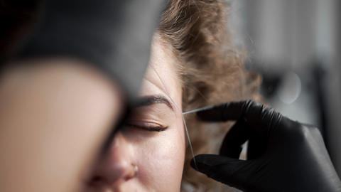 Removing small hairs from face with thread in beauty salon, depilation with Live Action