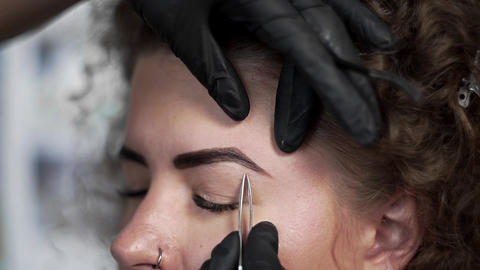 Correction of eyebrows shape by depilation by tweezers at the beauty salon Live Action