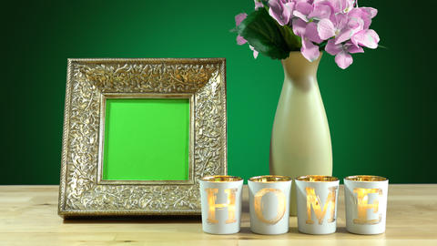 Antique photo frame with green screen and vase of flowers with burning home Footage