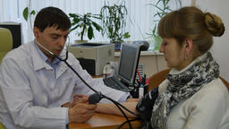 Family doctor measures patient's blood pressure Footage