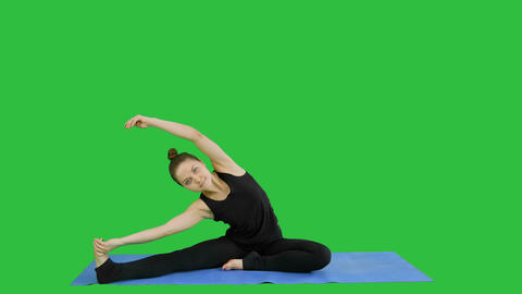 Young woman stretching her legs while doing yoga practice on a Green Screen Footage