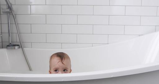 Little baby boy sits in bathtub, eyes Footage