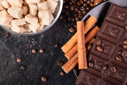 Top view of brown sugar, chocolate tablets and cinnamon sticks Photo
