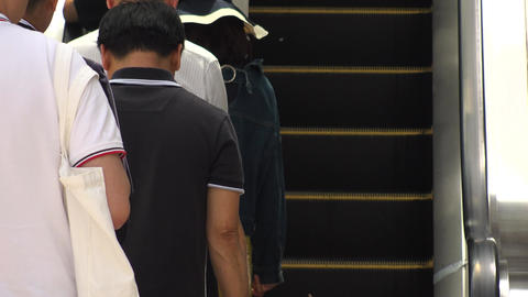 SHINJUKU, TOKYO, JAPAN - CIRCA MAY 2018 : BACK SHOT of PEOPLE using ESCALATOR Footage